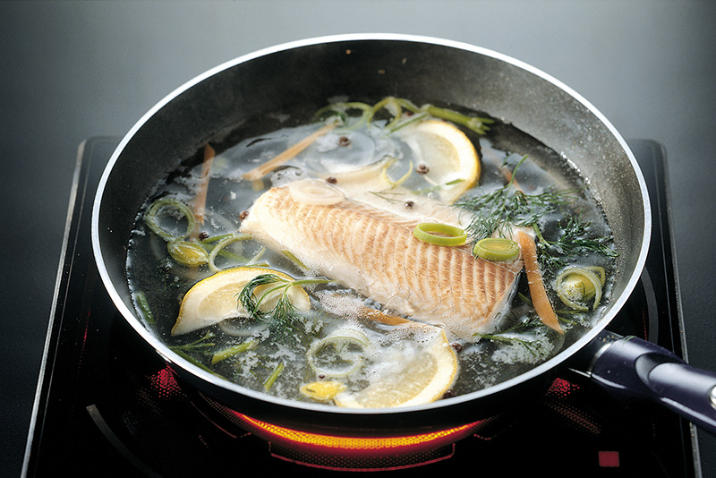 Kalaa keitetään pannulla mausteiden kanssa