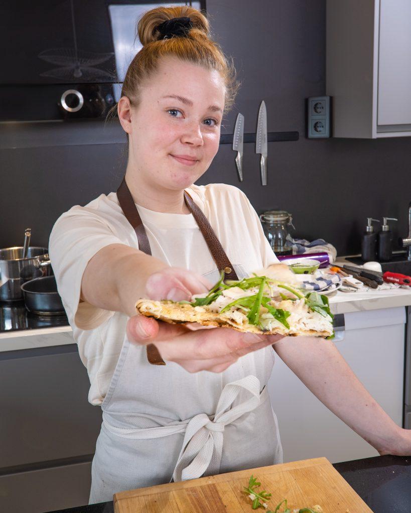 Anni Peräkylä ojentaa kalapizzaa